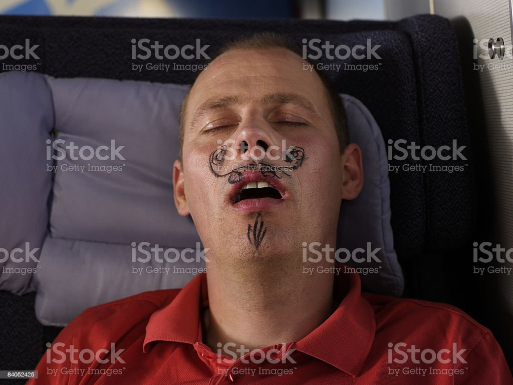 Sleeping man with drawn moustache royalty free stockfoto