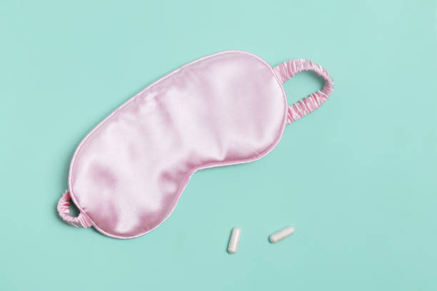Sleeping mask and pills on pastel green background. stock photo