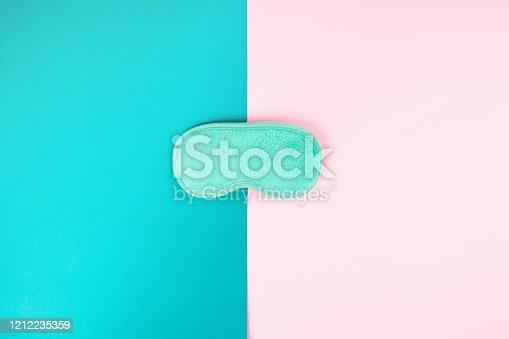 istock Sleeping mask on pink and turquoise duotone 1212235359
