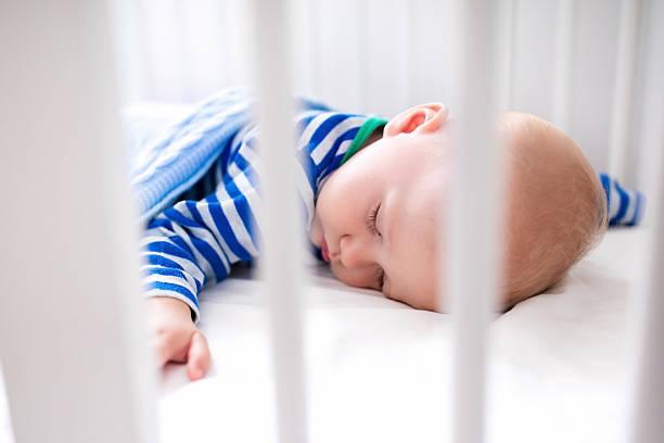 Sleeping newborn baby boy in white crib stock photo