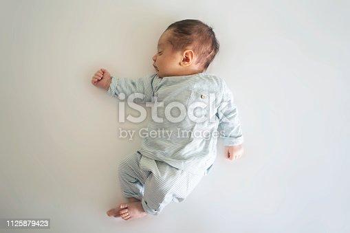 853843596 istock photo Sleeping newborn baby boy on bed. 1125879423