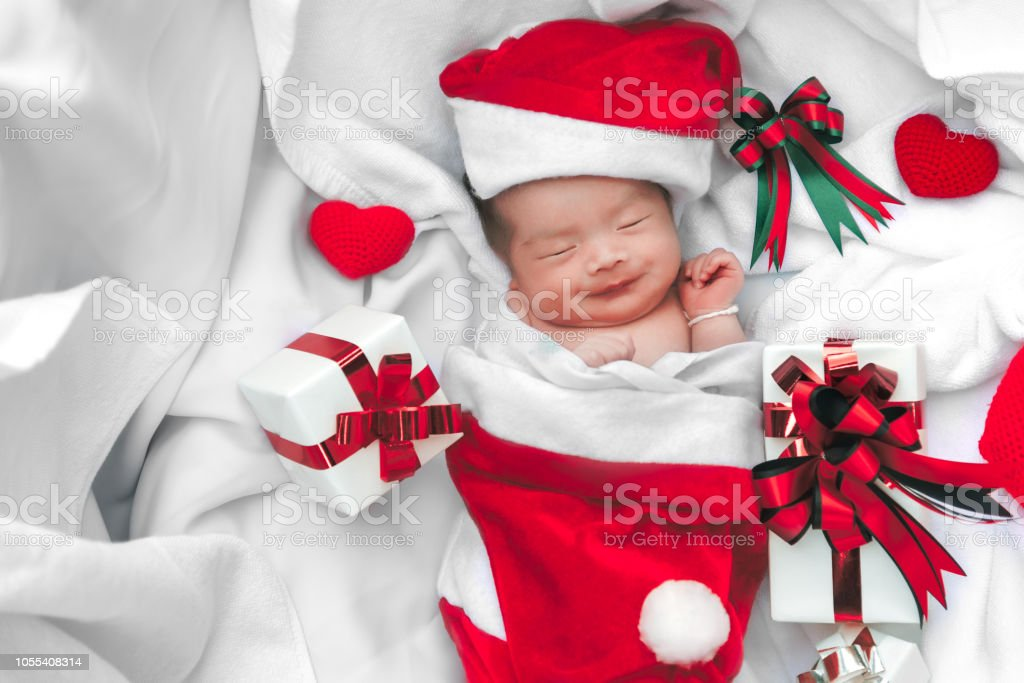 59cdcc79d Sleeping newborn baby face in Christmas hat with gift box from Santa Claus  and yarn heart on white soft towel. Cute Infant lifestyle and innocent  happy baby ...
