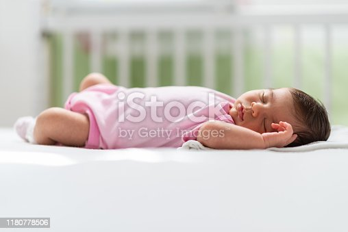 Close-up of a newborn baby girl peacefully sleeping in the crib.