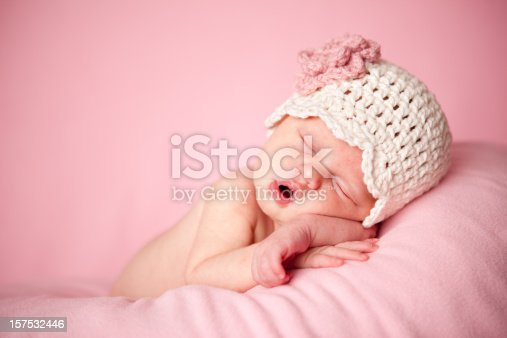 Color photo of a beautiful newborn baby girl wearing a crocheted hat while sleeping peacefully on a pink background.