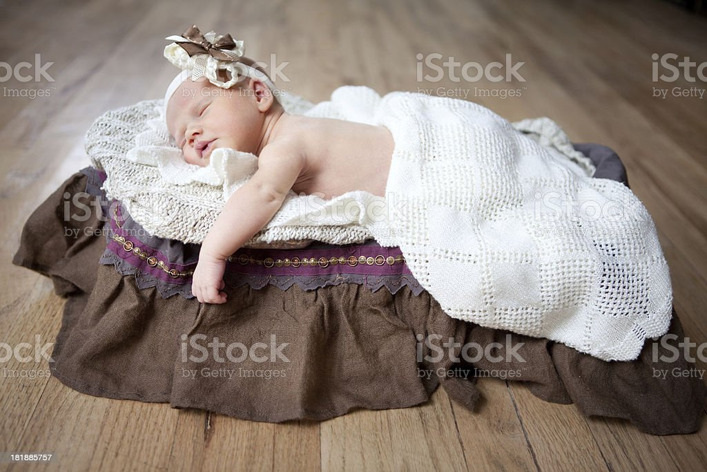 Sleeping Newborn Baby Girl with Headband on Wood Floor royalty-free stock photo