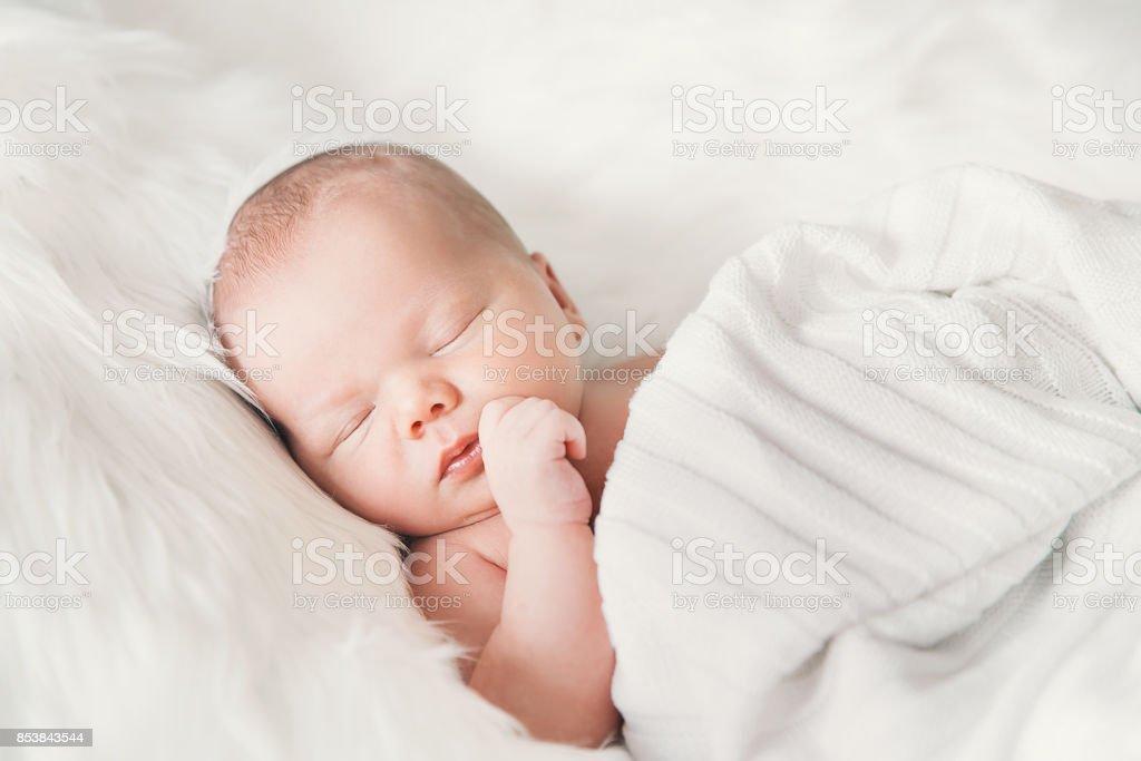 Bebé recién nacido durmiendo en una envoltura de manta blanca. - foto de stock