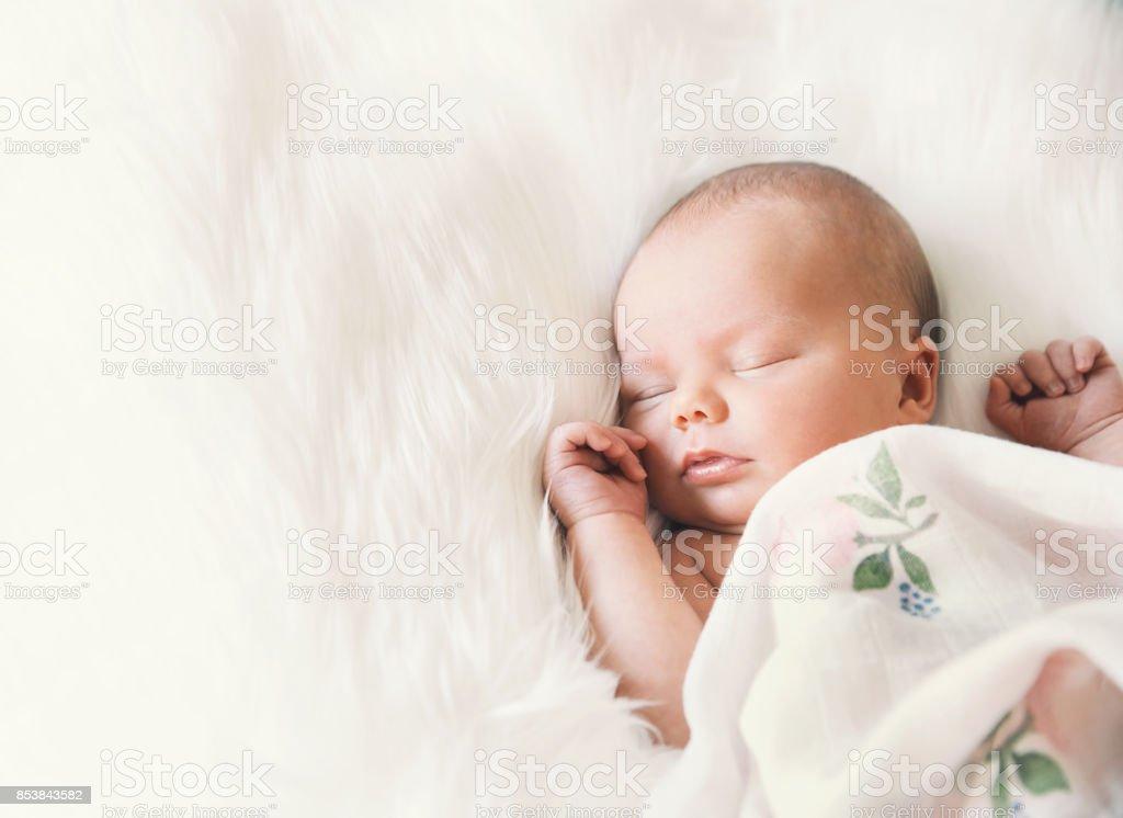 Sleeping newborn baby in a wrap on white blanket. stock photo