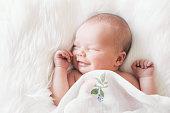 istock Sleeping newborn baby in a wrap on white blanket. 853843596