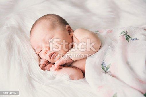 853843596 istock photo Sleeping newborn baby in a wrap on white blanket. 853843672