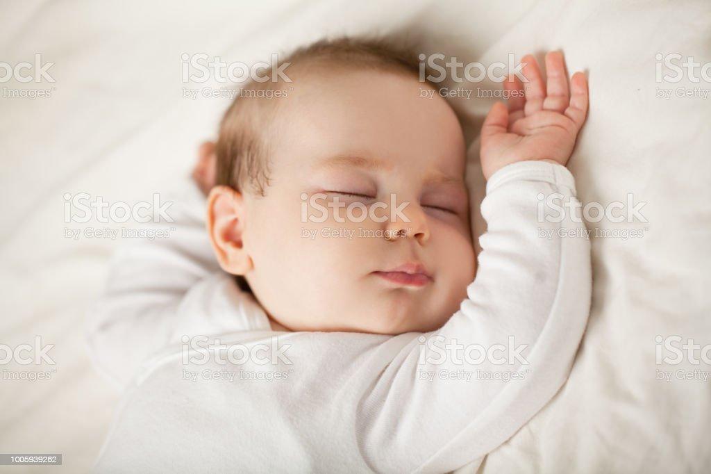 睡在白色背景下的新生嬰兒。小睡覺的孩子, 就寢時間 (嬰孩一個月)圖像檔