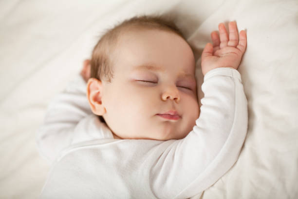 Sleeping newborn baby on white background. Small sleeping child, bedtime (baby up to one month) Sleeping newborn baby on white background. Small sleeping child, bedtime (baby up to one month) sleeping stock pictures, royalty-free photos & images