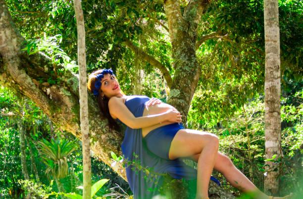 schwangere frau in einem park mit blauen drees hand auf bauch schlafen - drees und sommer stock-fotos und bilder