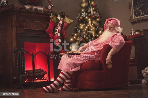 Santa Claus sits in a sofa chair in front of the fireplace in his living room, wearing pajamas with a plate of cookies and milk on his lap and a half eaten cookie in his hand, fast asleep, exhausted from delivering presents to all the boys and girls.