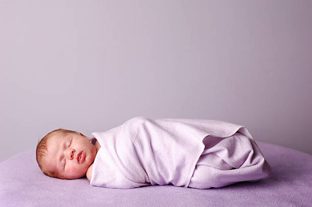 Sleeping, Swaddled Newborn Color photo of a beautiful little newborn baby swaddled and sleeping on a soft, purple blanket.  Room for text above. baby blanket stock pictures, royalty-free photos & images