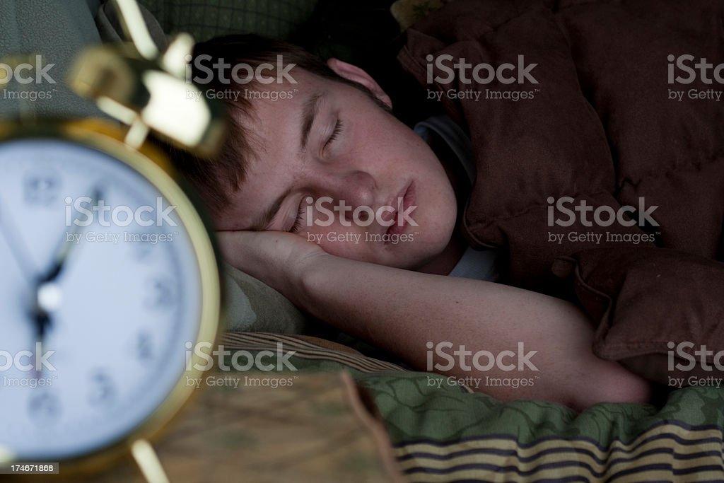 Dormir garoto adolescente com despertador - foto de acervo