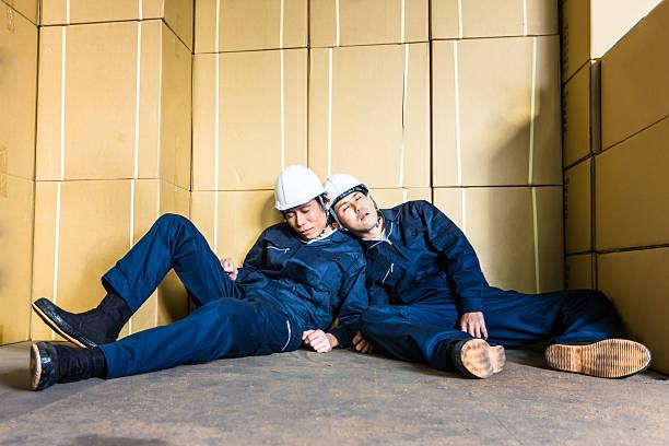 schlafen müde out arbeitnehmer zwischen pakete im warehouse - traum team stock-fotos und bilder