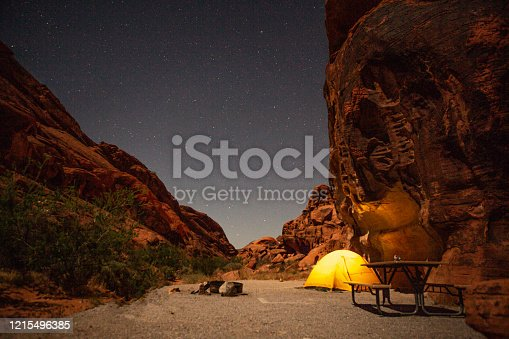 Night shot of Yellow tent pinched in red sandstone campsite in Valley of fire state park in Nevada USA
