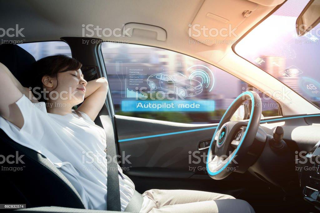 睡覺的女人在自動駕駛的汽車。自駕駛車輛。自動駕駛儀。汽車技術。圖像檔