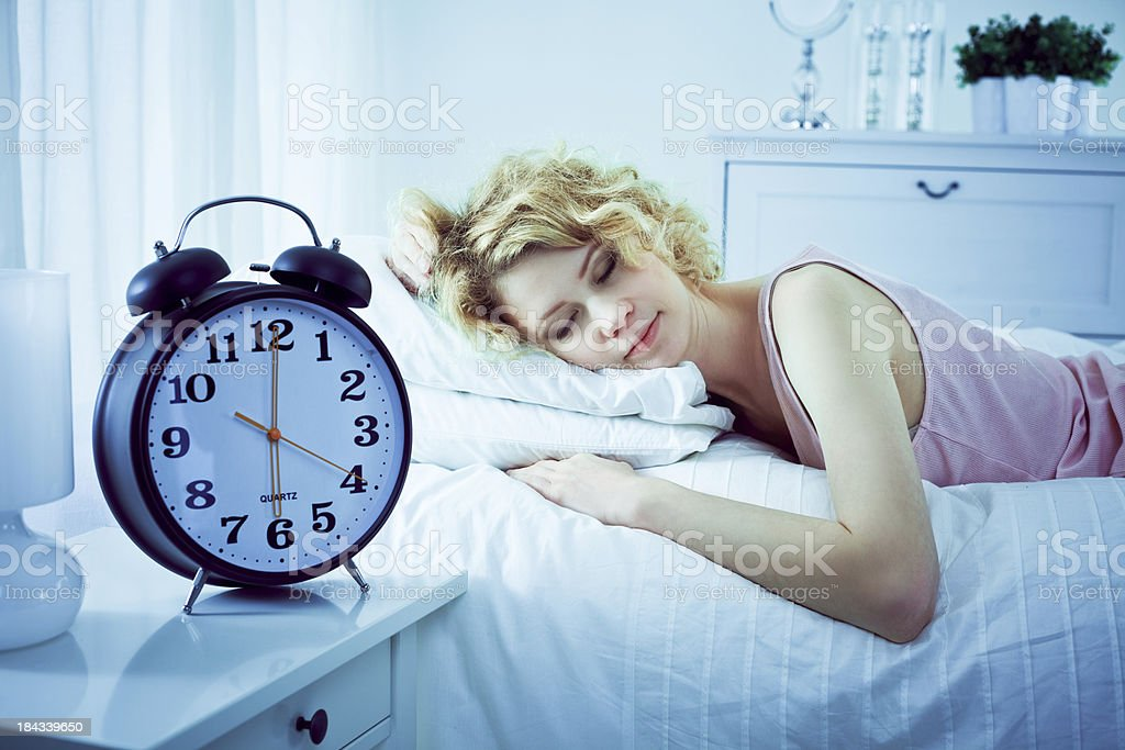 Sleeping woman Beautifull young adult woman sleeping blissfully in a bad on a white pillow at 6 a.m. In the foreground a big alarm clock. 20-24 Years Stock Photo