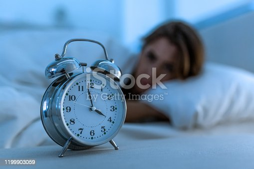 493155910 istock photo Sleepless and desperate beautiful caucasian woman awake at night not able to sleep, feeling frustrated and worried looking at clock suffering from insomnia in sleep disorder concept. 1199903059