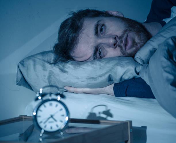 Schlaflose und verzweifelte junge kaukasische Mann wach in der Nacht nicht in der Lage zu schlafen, gefühl frustriert und besorgt Blick auf Uhr leiden an Schlaflosigkeit in Stress und Schlafstörung Konzept. – Foto