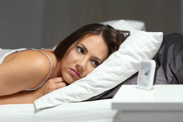 Sleepless insomniac girl looking at alarm clock in the night stock photo