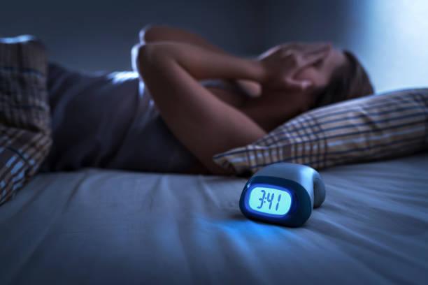 schlaflose frau, die an schlaflosigkeit, schlafapnoe oder stress leidet. müde und erschöpfte dame. kopfschmerzen oder migräne. mitten in der nacht aufwachen. frustrierte person mit problem. wecker. - besorgt stock-fotos und bilder