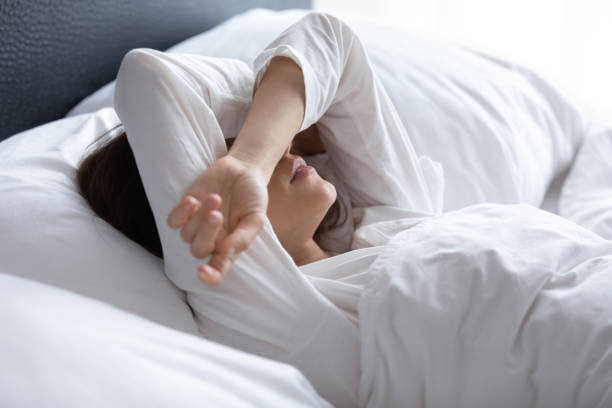 Sleepless young woman suffering from insomnia, covering eyes with hands stock photo
