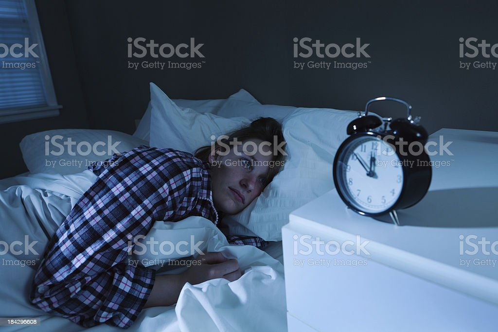 Sleepless Young Woman with Insomnia in Bed, Watching Alarm Clock stock photo