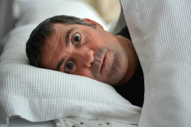 sleeplessness man - fear stock photos and pictures