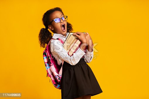 istock Sleepy African American Schoolgirl Yawning Carrying Books, Yellow Background 1174499605