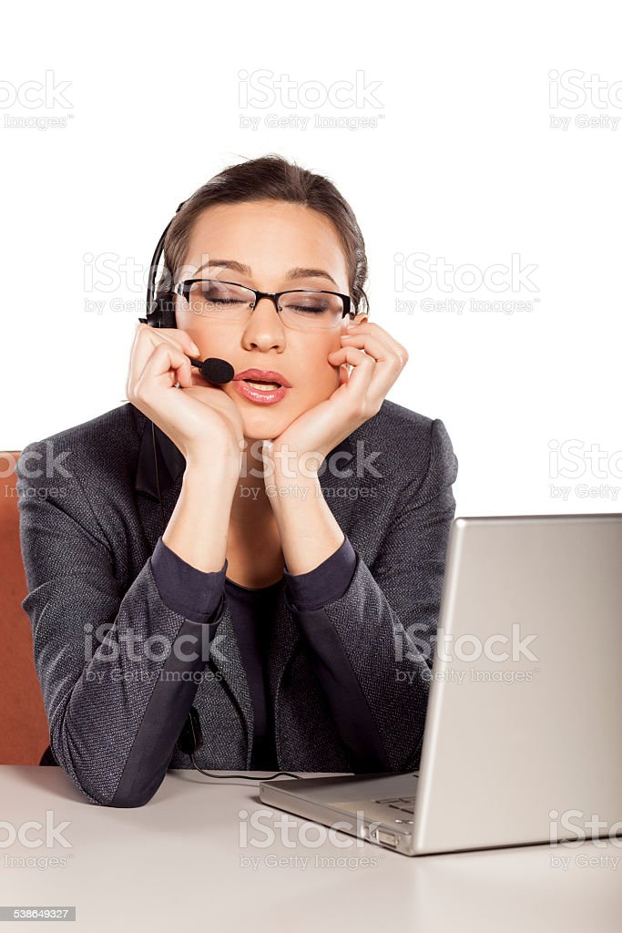 Sleepy and tired girl working in call center stock photo