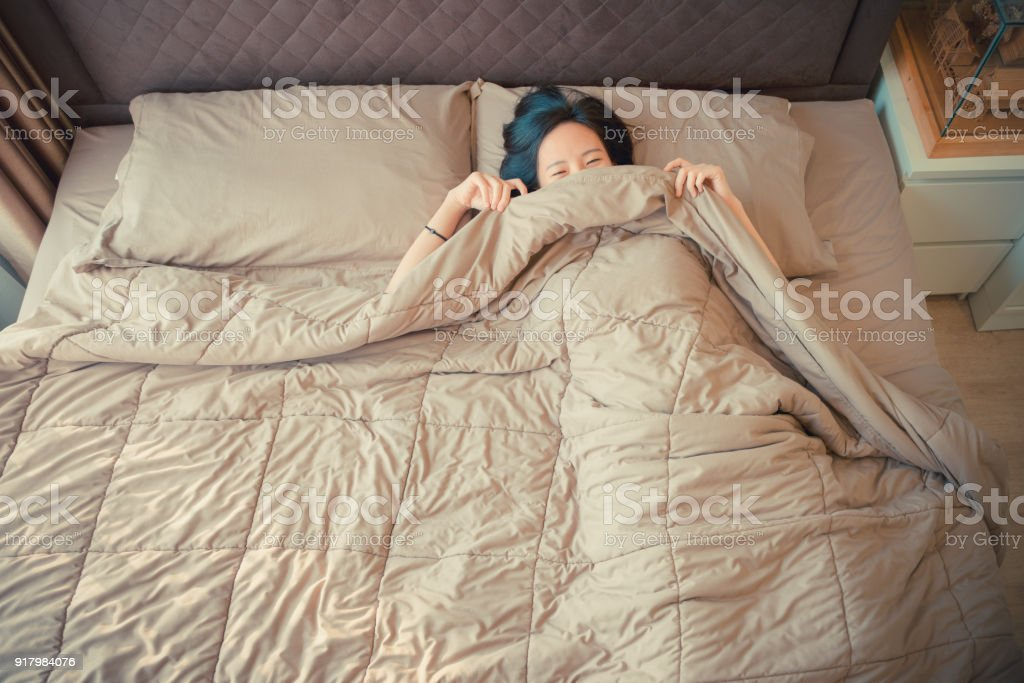 Sleepy Asian woman lying on bed, top view stock photo