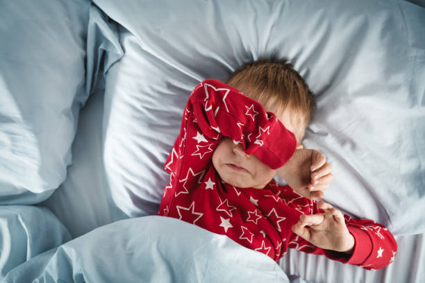 Sleepy boy lying in bed with blue beddings stock photo