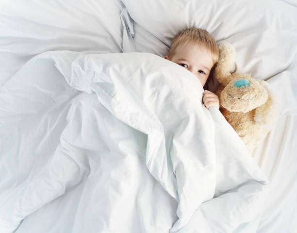 Sleepy boy lying in bed with white beddings stock photo