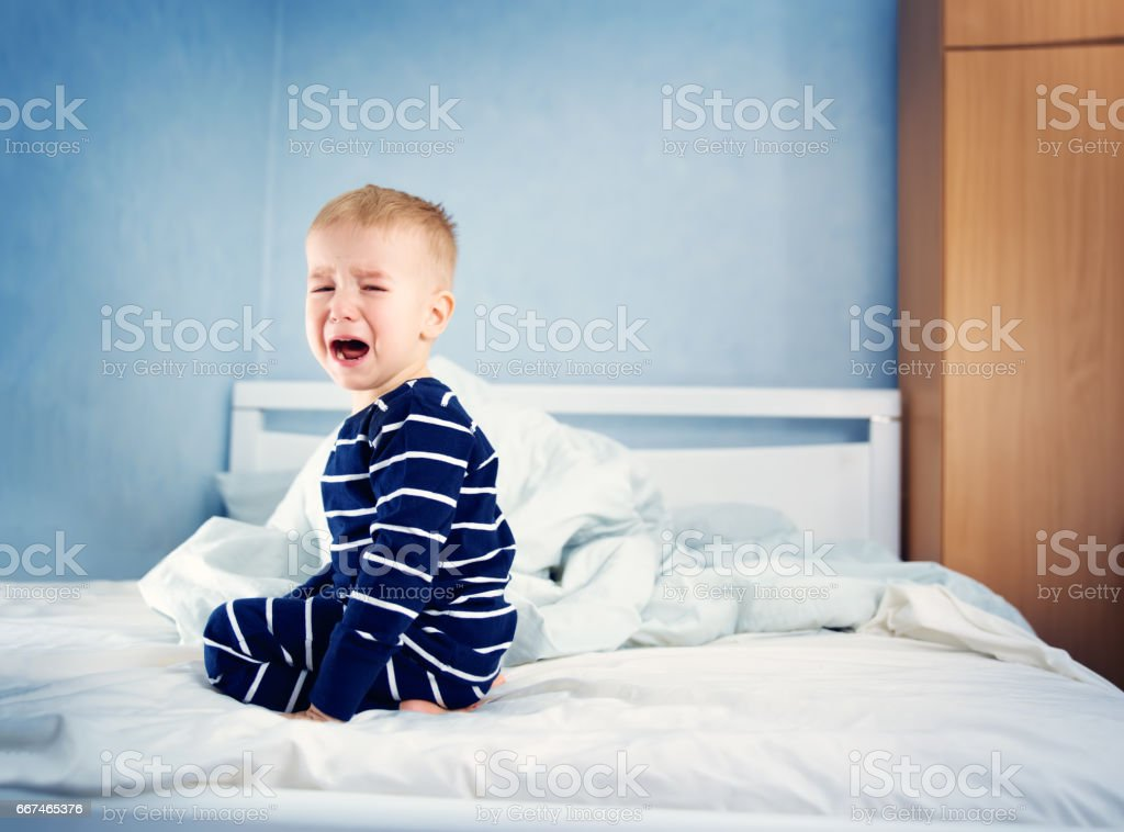 Sleepy boy sitting in bed stock photo