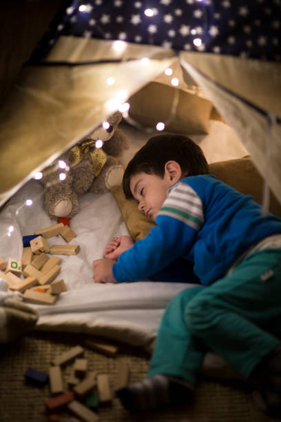 Sleepy boy taking a nap inside of a tent at home stock photo