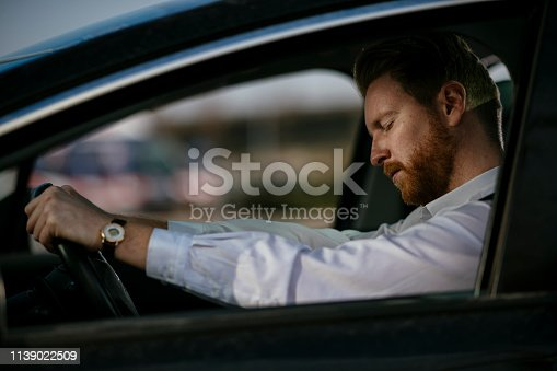 Sleepy businessman driving car. Shadow DOF. Developed from RAW; retouched with special care and attention; Small amount of grain added for best final impression. 16 bit Adobe RGB color profile.