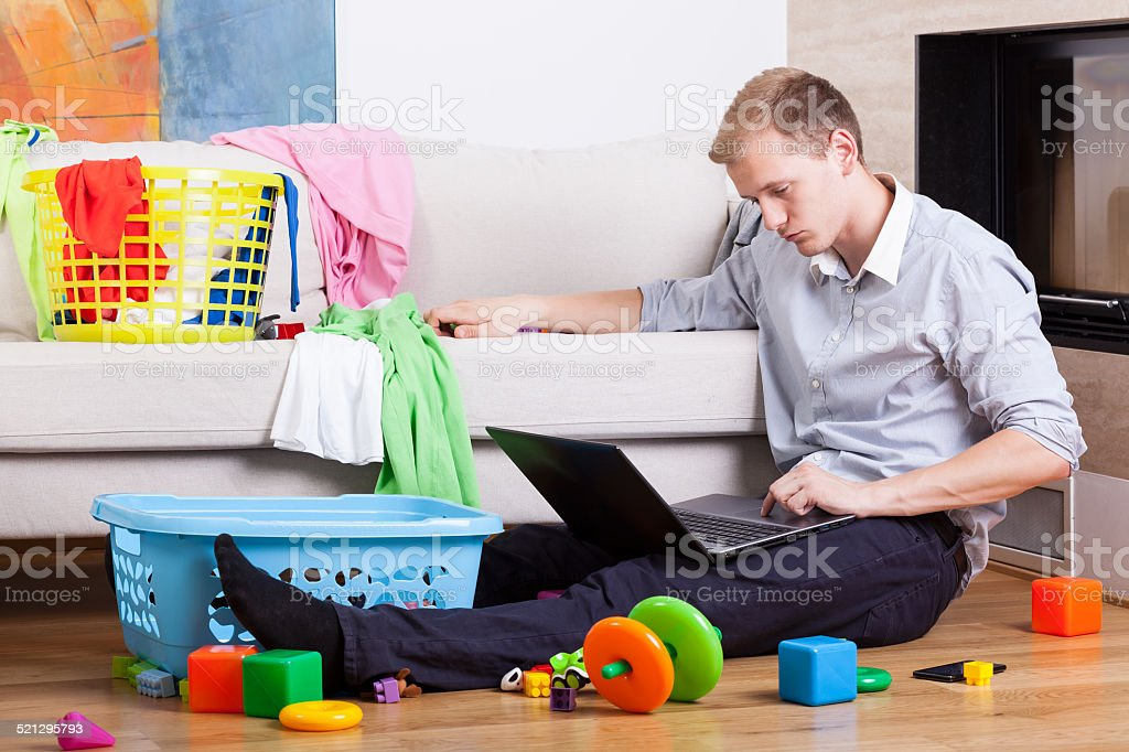 Sleepy father trying to work stock photo