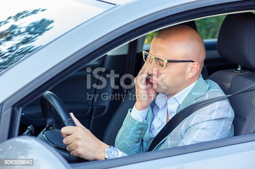 istock Sleepy fatigued exhausted young man driving his car in traffic after long hour drive. 936359640