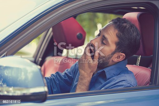 istock sleepy fatigued yawning exhausted young man driving his car 663161810