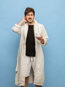 Sleepy young man in white bathrobe, home clothing with cup of coffee standing isolated on blue background. Concept of human emotions, facial expression, home interior. Copy space for ad.