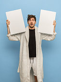 Surprised. Shocked man in white bathrobe, home clothing with blank sheets of paper isolated on blue background Concept of human emotions, facial expression, home interior. Copy space for ad.