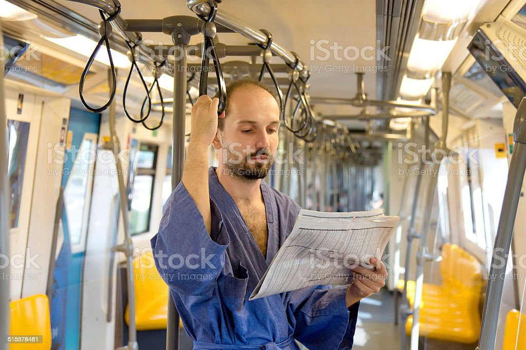 sleepy man reading a newspaper on the subway stock photo