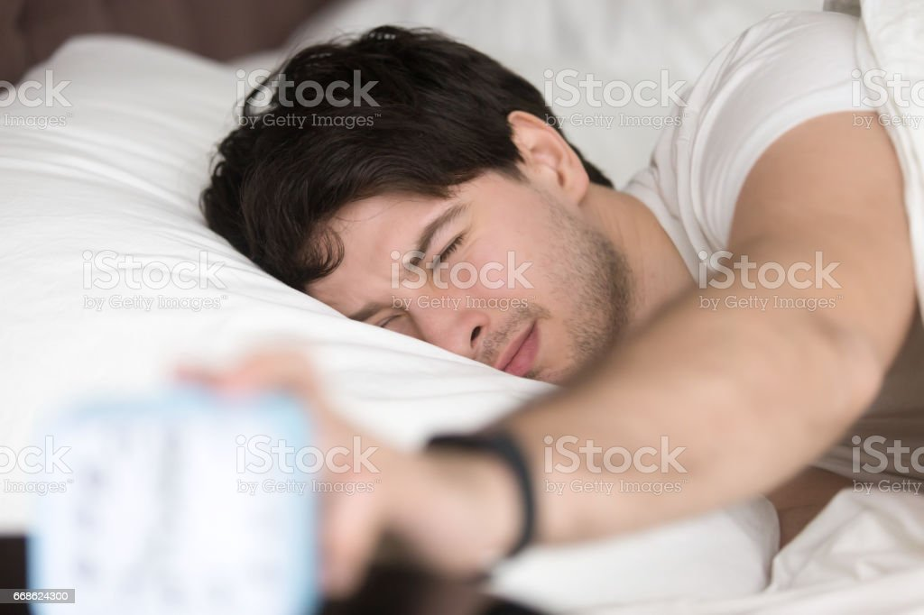Sleepy man turning off alarm clock, time to wake up - foto de acervo
