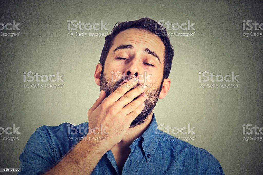 Sleepy man yawning isolated on gray background stock photo