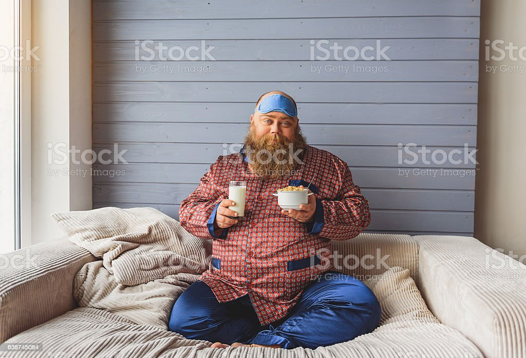 Sleepy thick guy eating cereals with milk stock photo