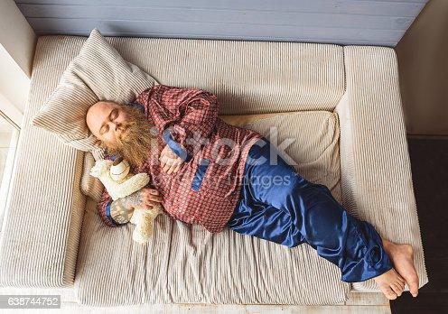 istock Sleepy thick guy lying on couch 638744752