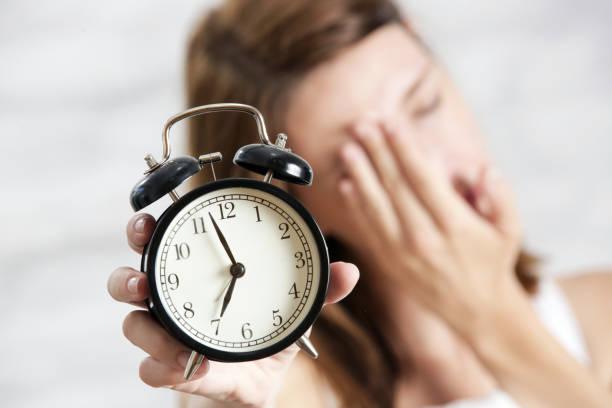 Schlafmüde Frau hält Wecker, sieben Uhr morgens, kein Frühbucherkonzept – Foto