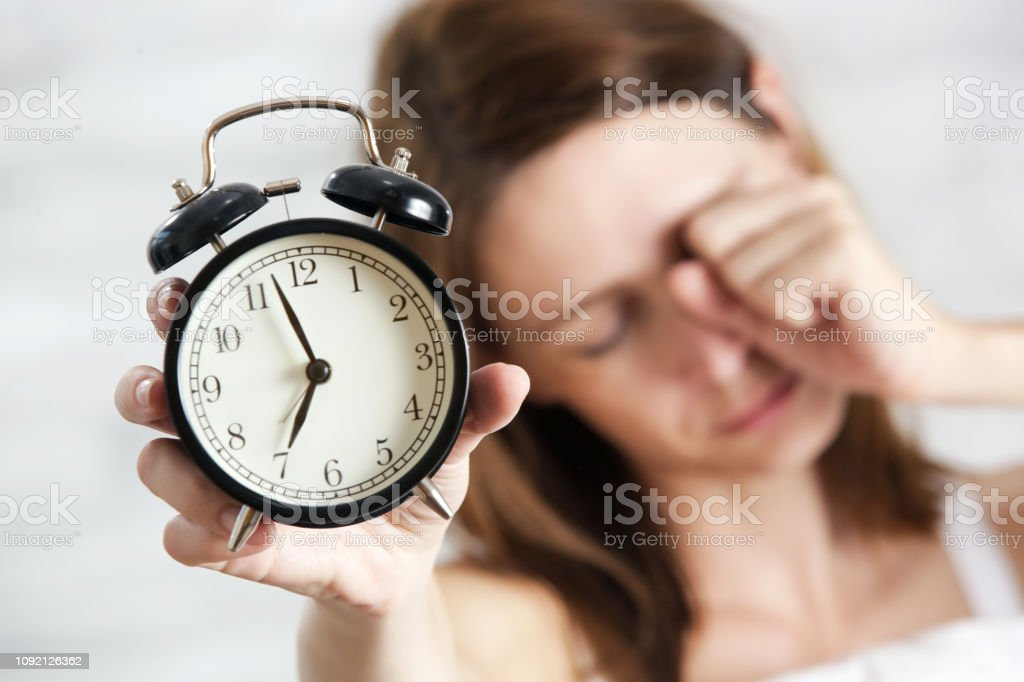 Sleepy tired woman holding alarm clock, seven o\'clock in the morning,...